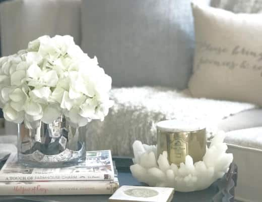 Tufted velvet cream tuxedo sofa with textured ivory blanket and oversized gray pillows with black distressed coffee tray and gold candle, white hydrangeas in mercury glass and books with anthropologie coasters